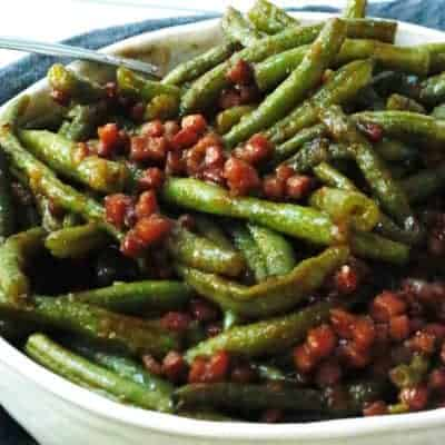 A white bowl of barbecued green beans with diced hams and onions
