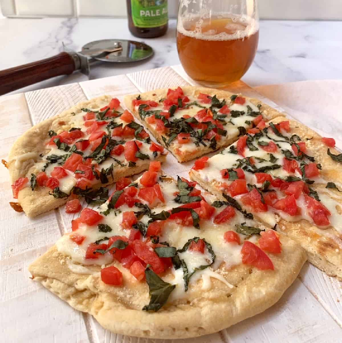 A sliced personal pizza with a glass of beer and a pizza cutter.