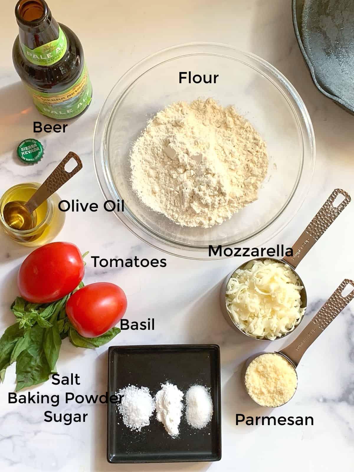 Flour, cheese, tomatoes, basil, oil,beer to make a pizza dough.