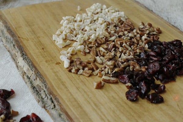 candied ginger, chopped pecans, and dried cranberries on a cutting board