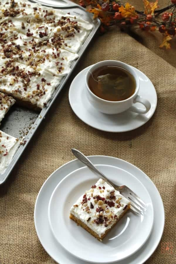 A slice of pumpkin sheet cake with a cup of tea.