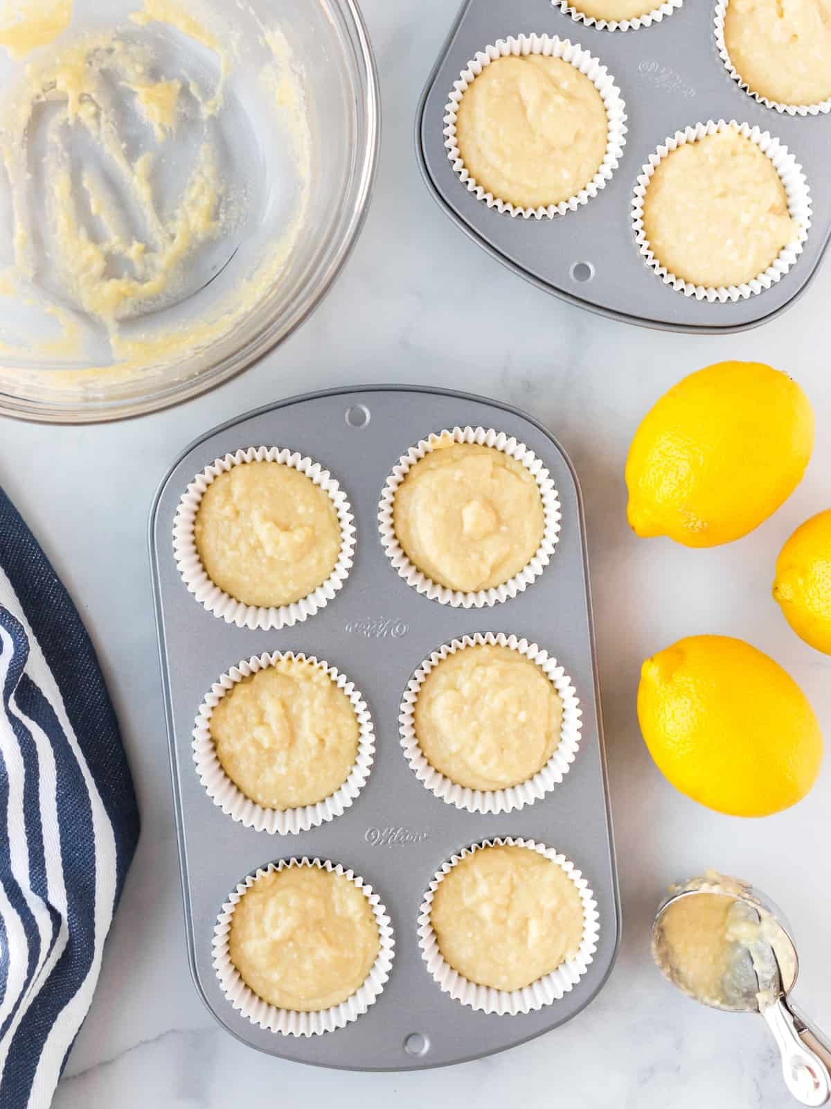 Muffin batter in muffin pans with lemons.