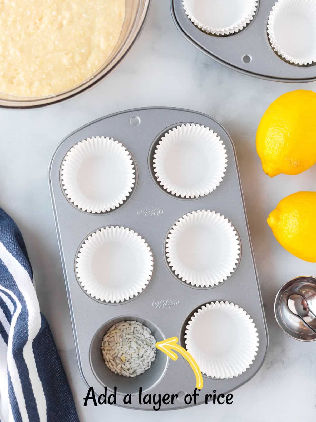 A paper-lined muffin tin with rice in one cup.