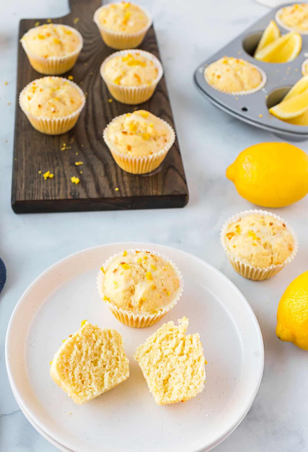 Cut open lemon muffins on a white plate.