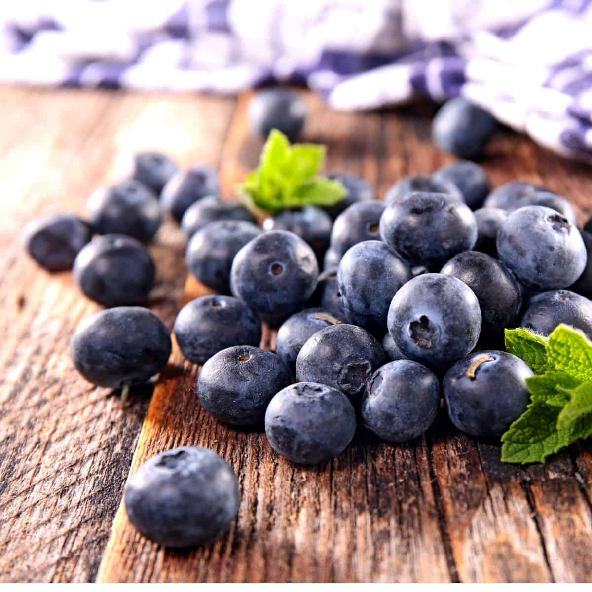 Fresh blueberries on a wooden board.