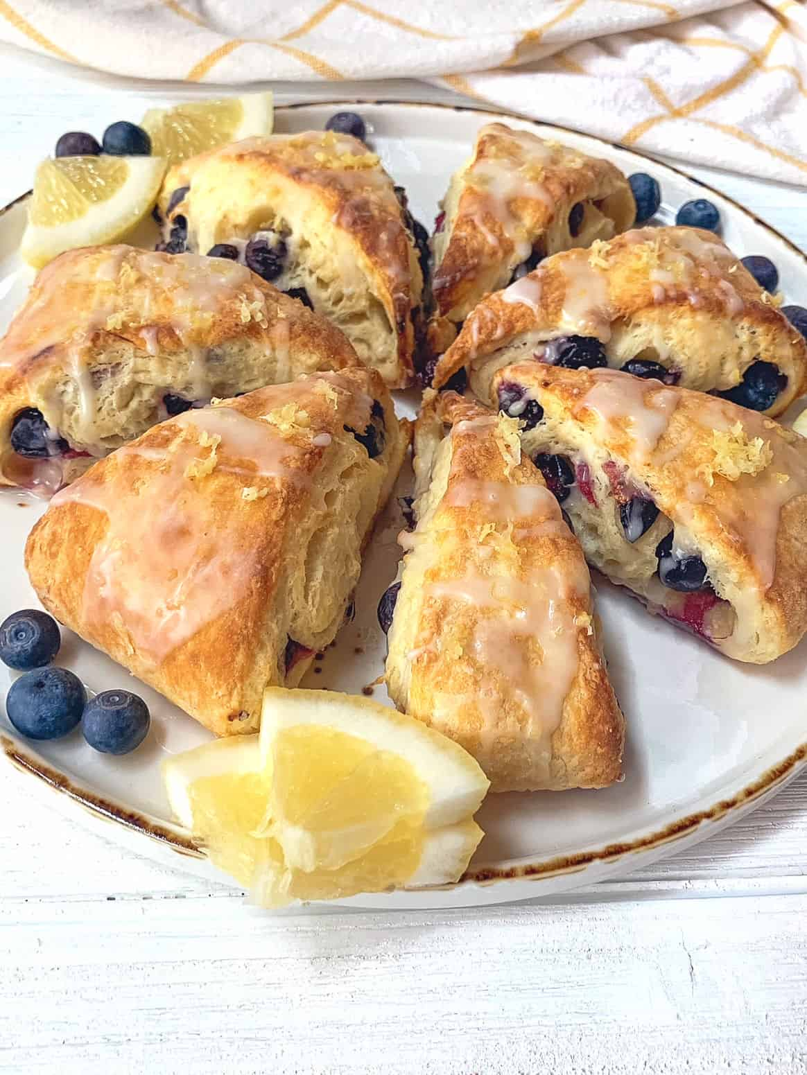 A white plate filled with blueberry scones.