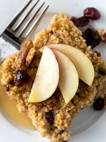 A square of oatmeal with apples and cranberries with maple syrup.