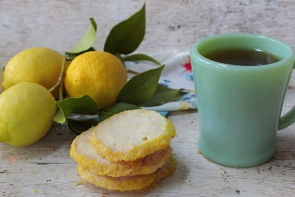 Crispy lemon shortbread cookies with a cup of tea next to three fresh lemons