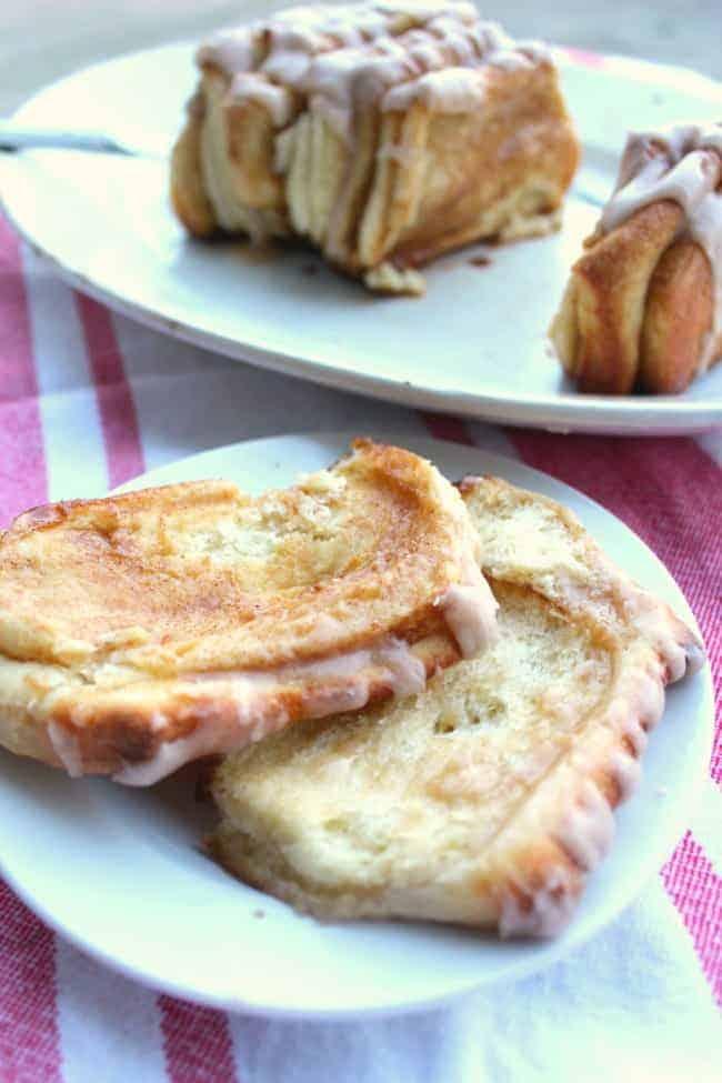 Slices of cinnamon sugar pull apart bread on white plates.
