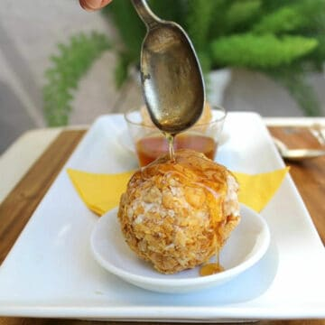 Drizzling honey over a cereal coated ice cream ball.