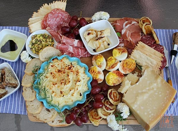 A meat and cheese board with salamis, eggs, baked ricotta and Parmesan cheese