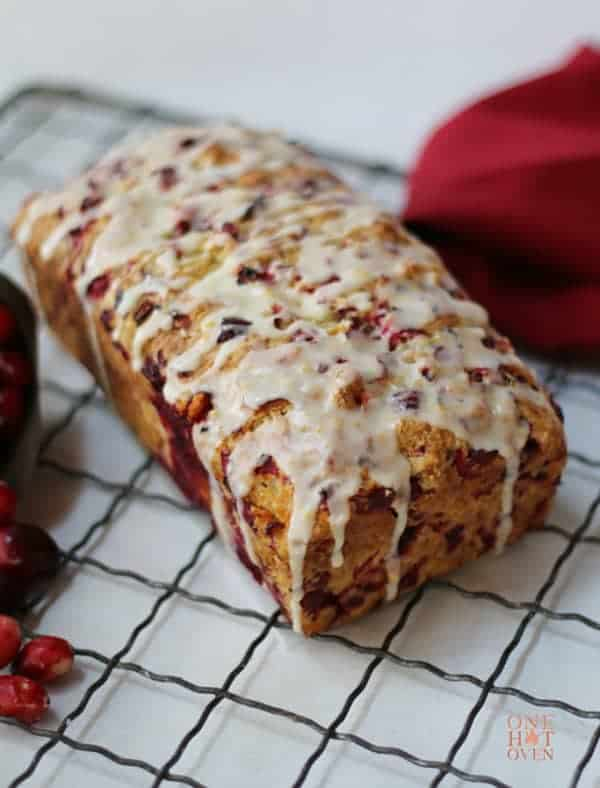 A loaf of glazed Cranberry Orange Bread on a cooling rack