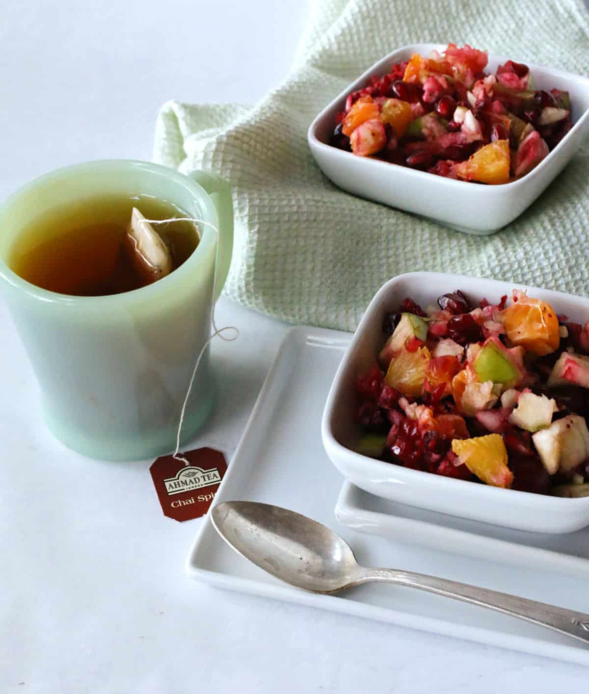 a cup of tea and bowls of fruit salad