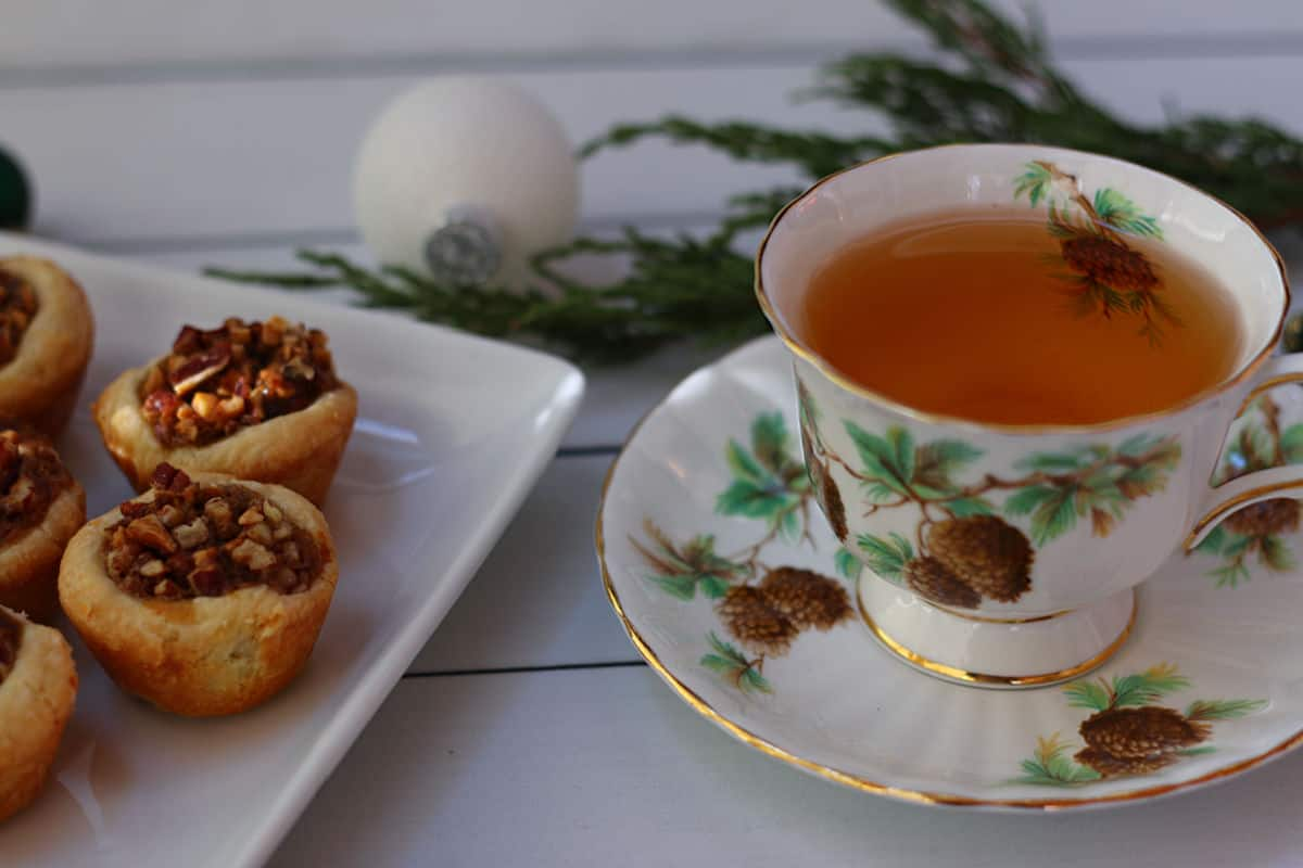 Pecan Tassies on a white plate and a cup of tea