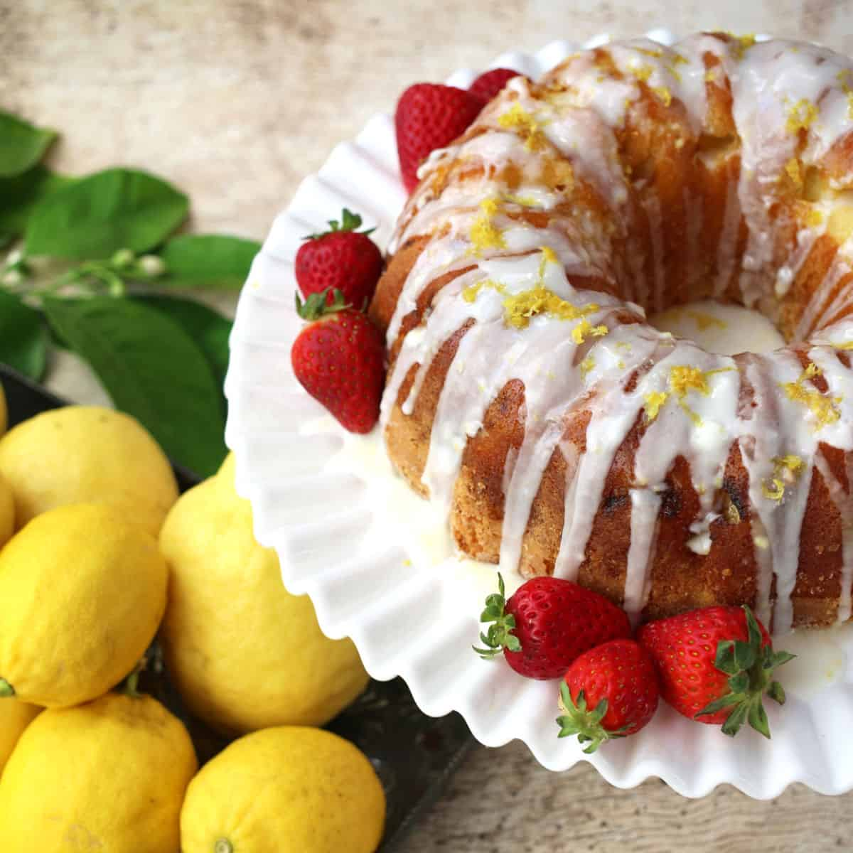 A lemon bundt cake with vanilla frosting and strawberries.