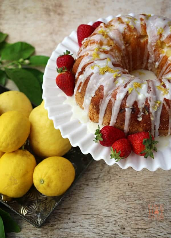 Iced Sweet and Tangy Lemon Cake sitting a a milk glass cake stand