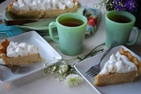 Two slices of butterscotch pie with cups of tea