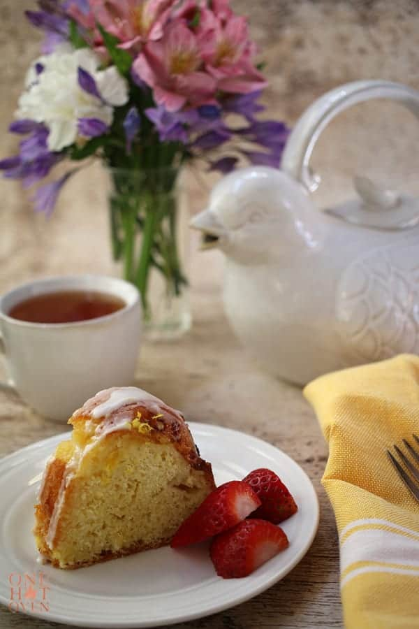 Fresh baked lemon cake with berries and a cup of tea