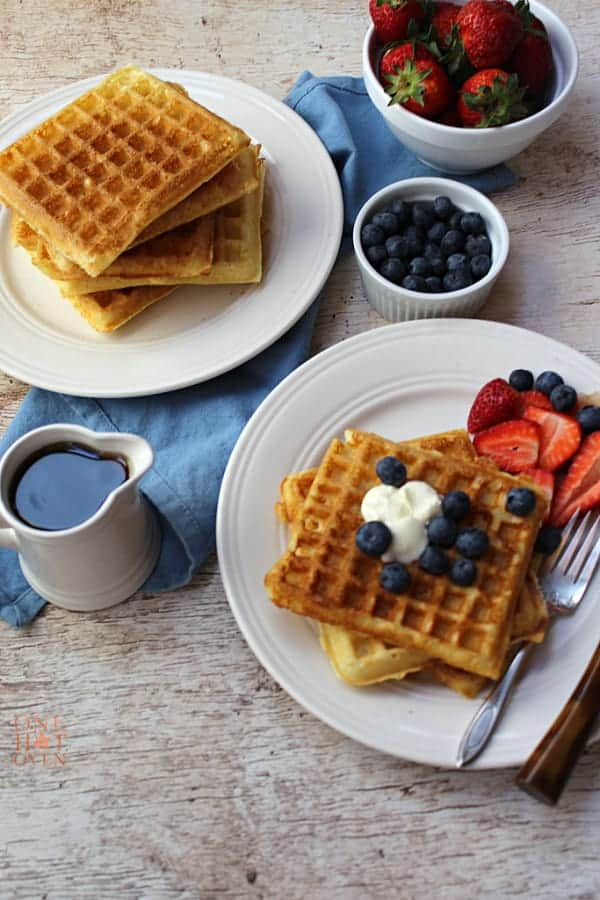 plates of waffles, syrup and blueberries