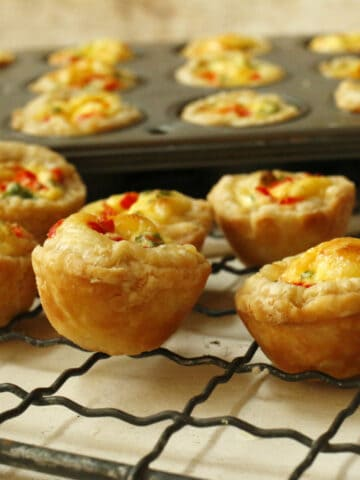 A cooling rack with mini swiss cheese quiches.