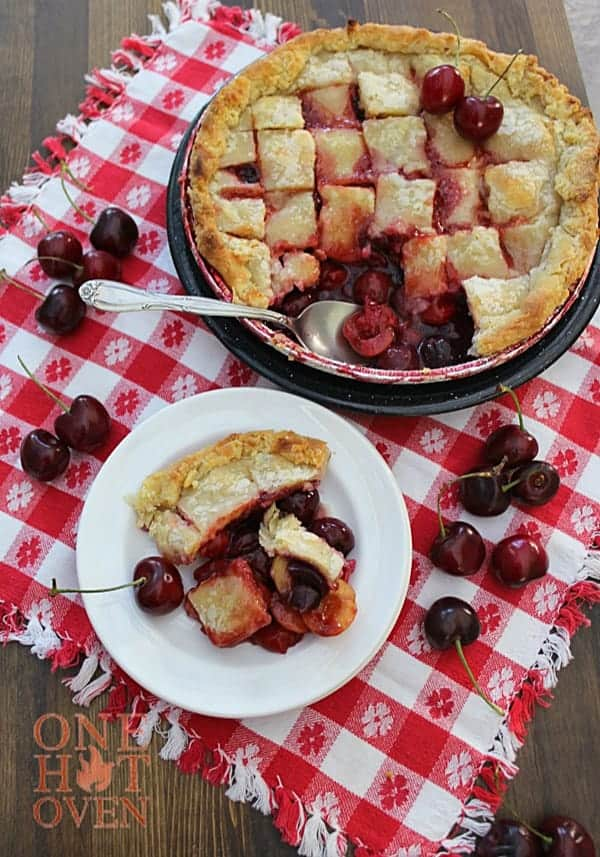 A grilled cherry pandowdy with a golden flaky pie crust and fresh red cherries
