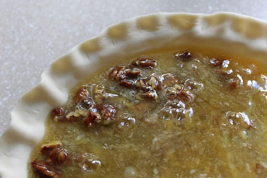 A pie with unbaked pecan pie filling