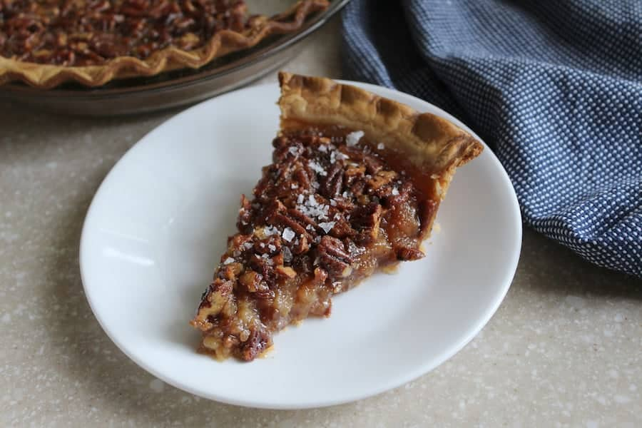 A slice of bourbon pecan pie on a white plate