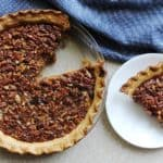 A bourbon pecan pie with a slice of pie on a white plate