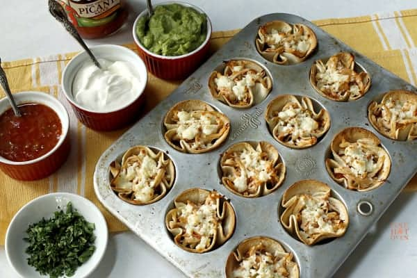 baked mini chicken taco cups in a muffin pan with salsa, sour cream, guacamole and cilantro