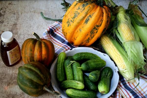 Acorn squash, pickling cucumbers, honey, yellow corn and a green and yellow pumpkin