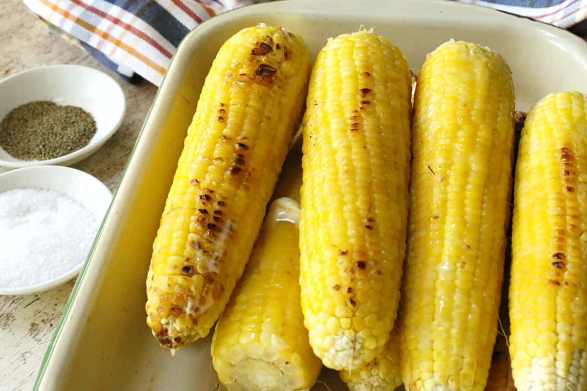 Ears of grilled corn in a white tray.