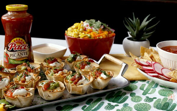 A tray of mini chicken taco cups and a corn salad with Pace Picante Sauce