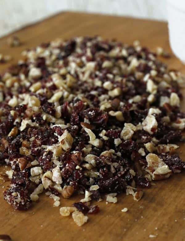 a cutting board with chopped pecans, cranberries and ginger