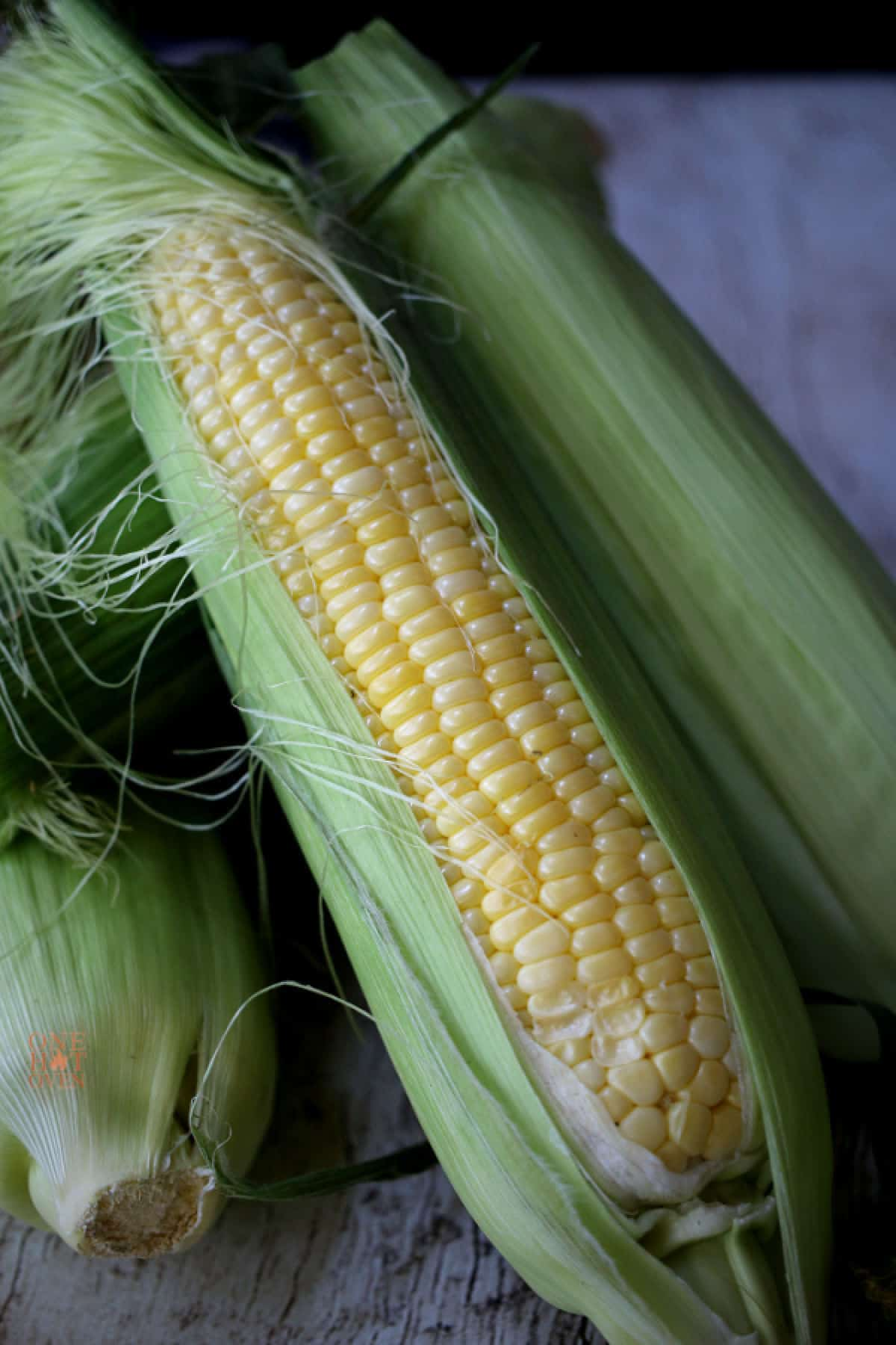 Corn on the cob in the husks.