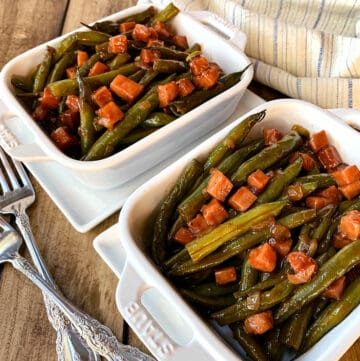 Green beans and ham in white dishes.