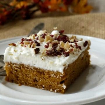 A slice of Spicy Pumpkin Sheet Cake with White Chocolate Cream Cheese Frosting topped with sprinkles of cranberries, pecans and ginger
