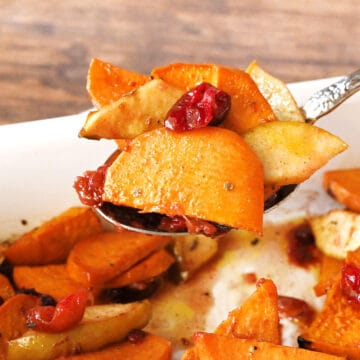 A spoonful of baked sweet potatoes with apples and cranberries.