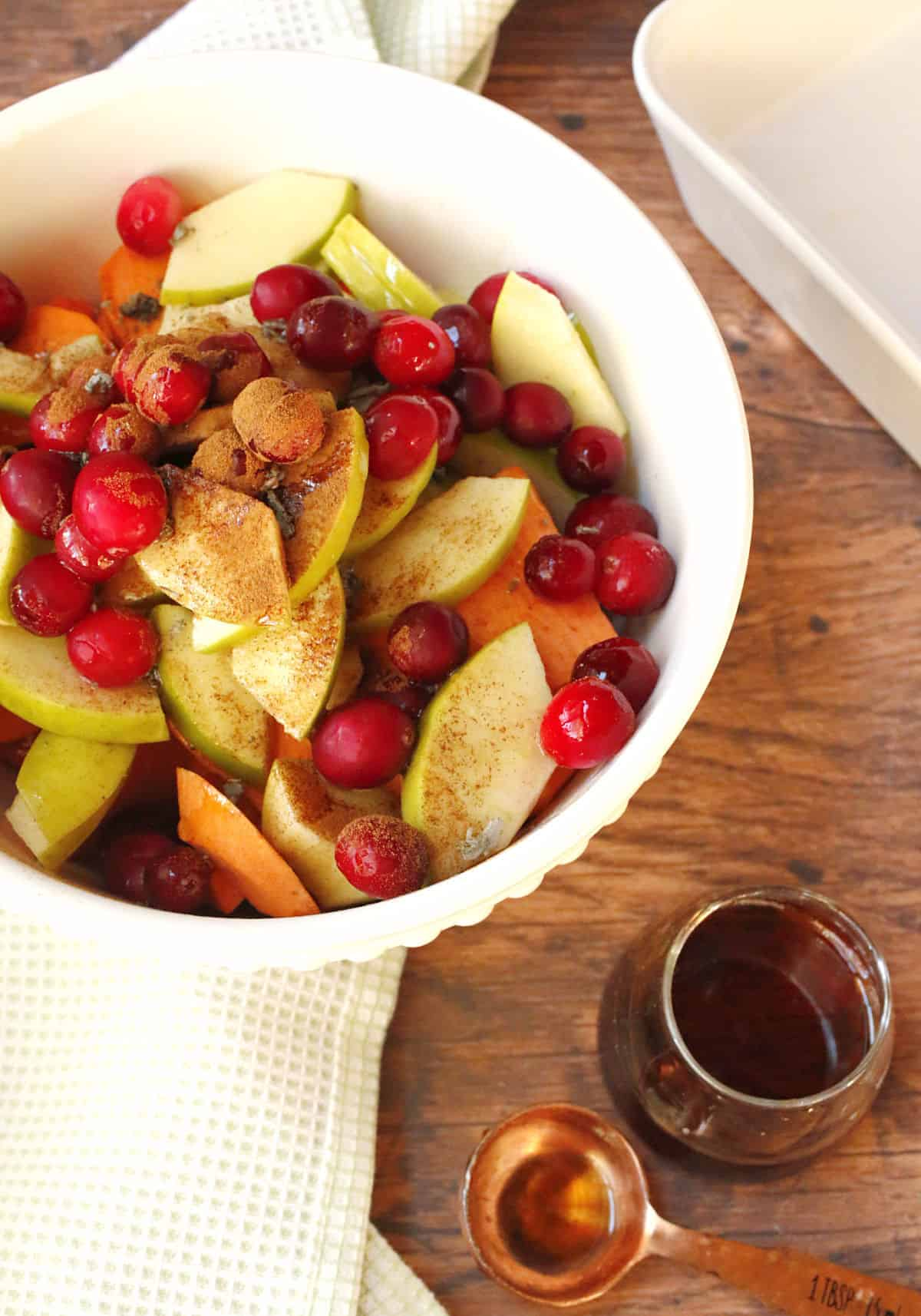 A mixing bowl filled with slices of sweet potatoes, apples and cranberries.