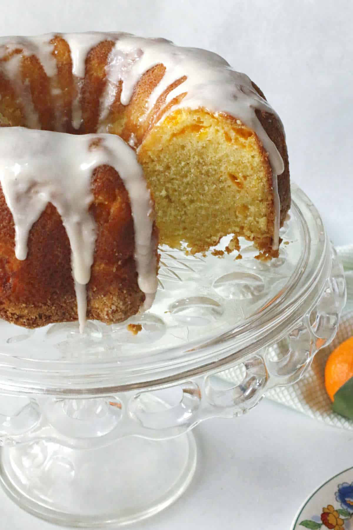 A mandarin orange cake on a cake stand.