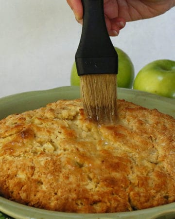 Brushing butter on a baked apple scone.