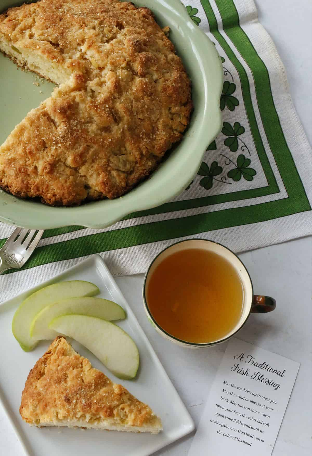 Irish Apple Scones on a white plate and a cup of hot tea.