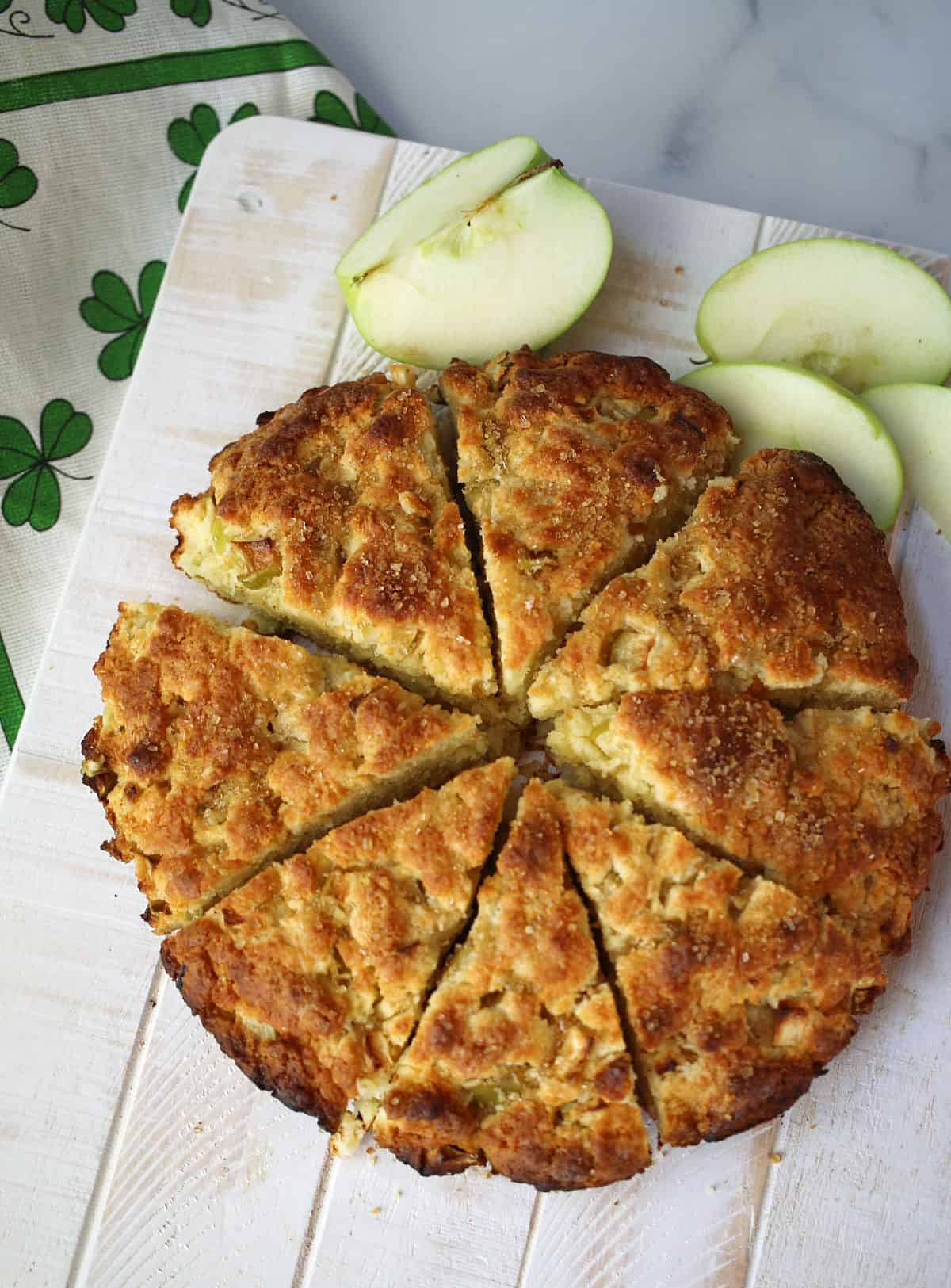 Baked apple scones cut in wedges on a white cutting board.