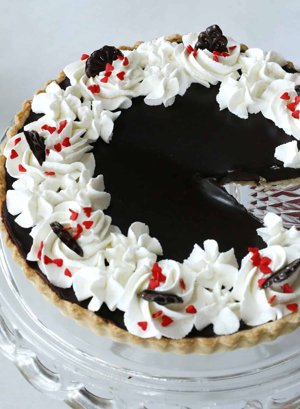 a chocolate tart with whipped cream and candy red hearts