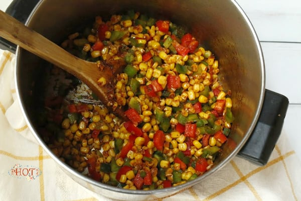 Corn and peppers cooking in soup pot