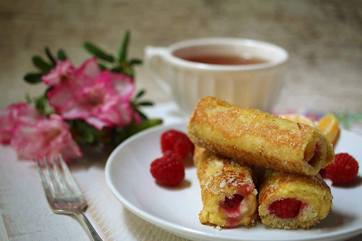 a plate of raspberry french toast roll ups