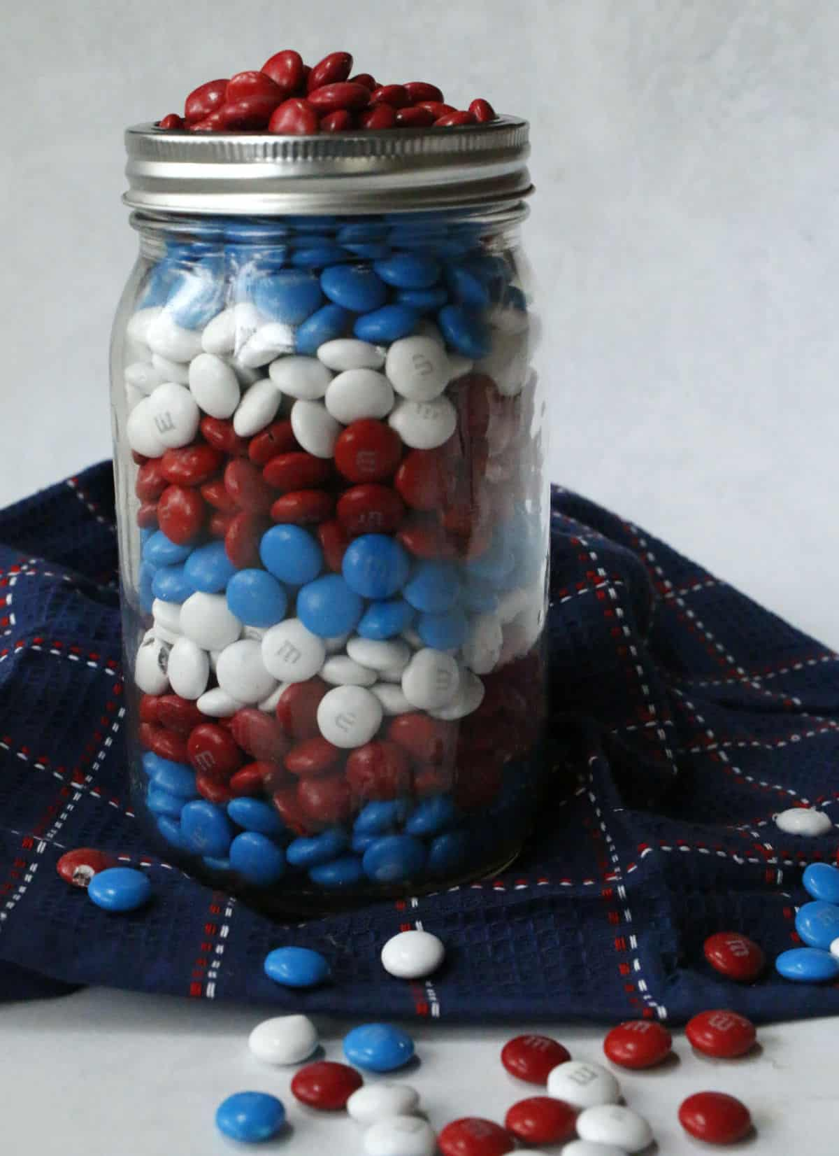 A mason jar of red, white and blue M & Ms.