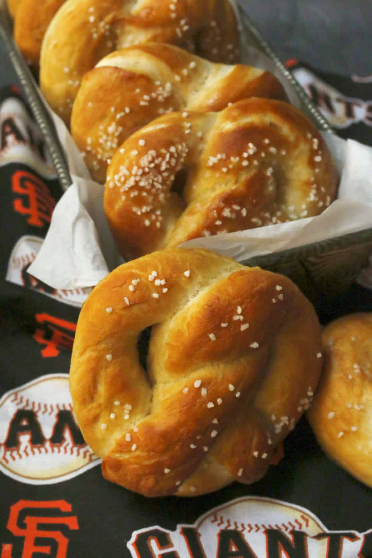 A pan filled with salted pretzels on a San Francisco Giants towel.