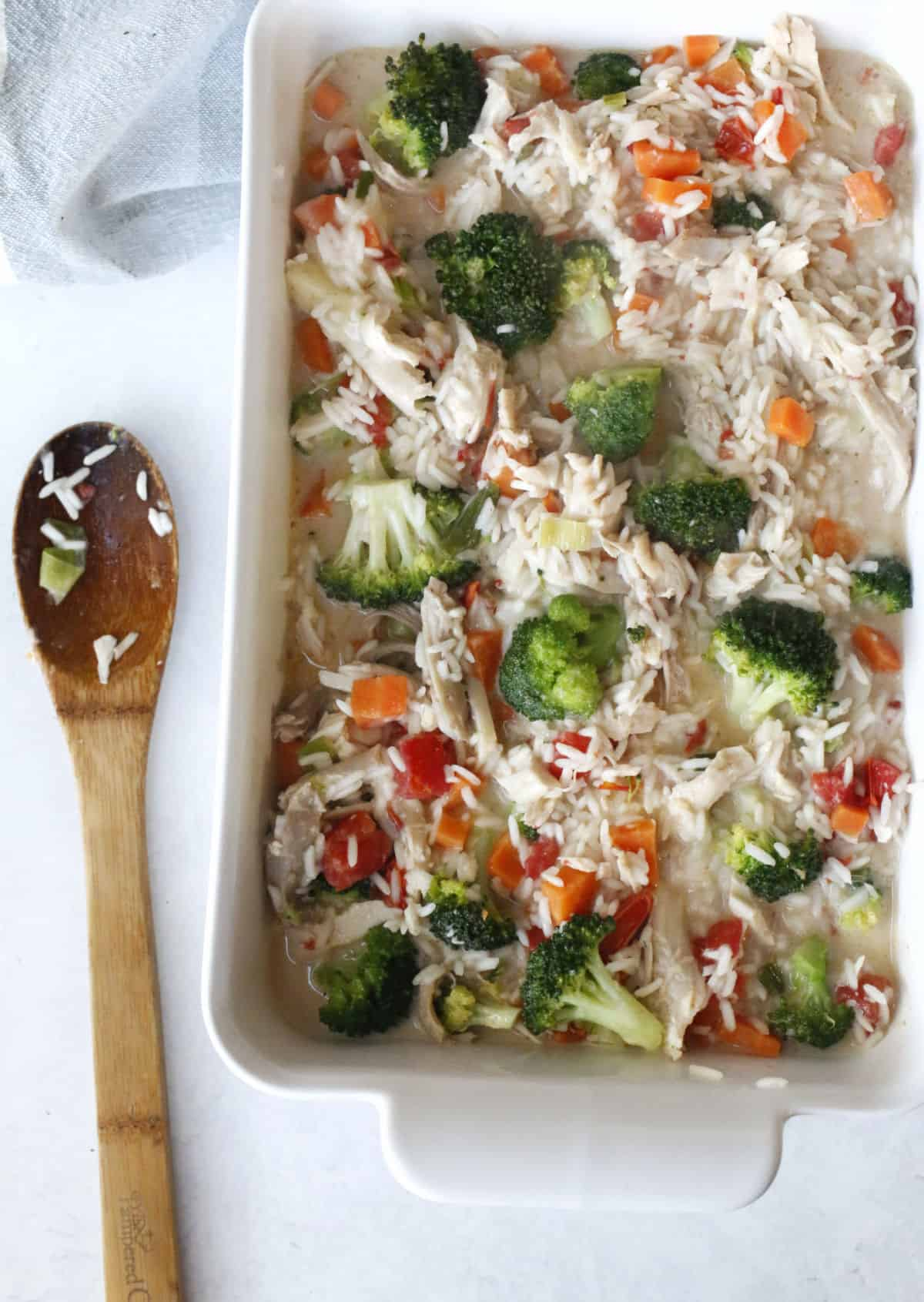 a baking dish filled with chicken and rice casserole ready to bake