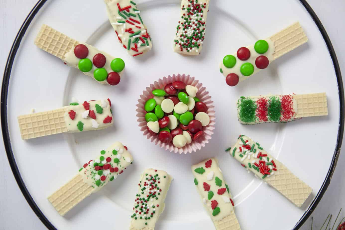 a white plate of chocolate dipped Christmas sugar wafer cookies