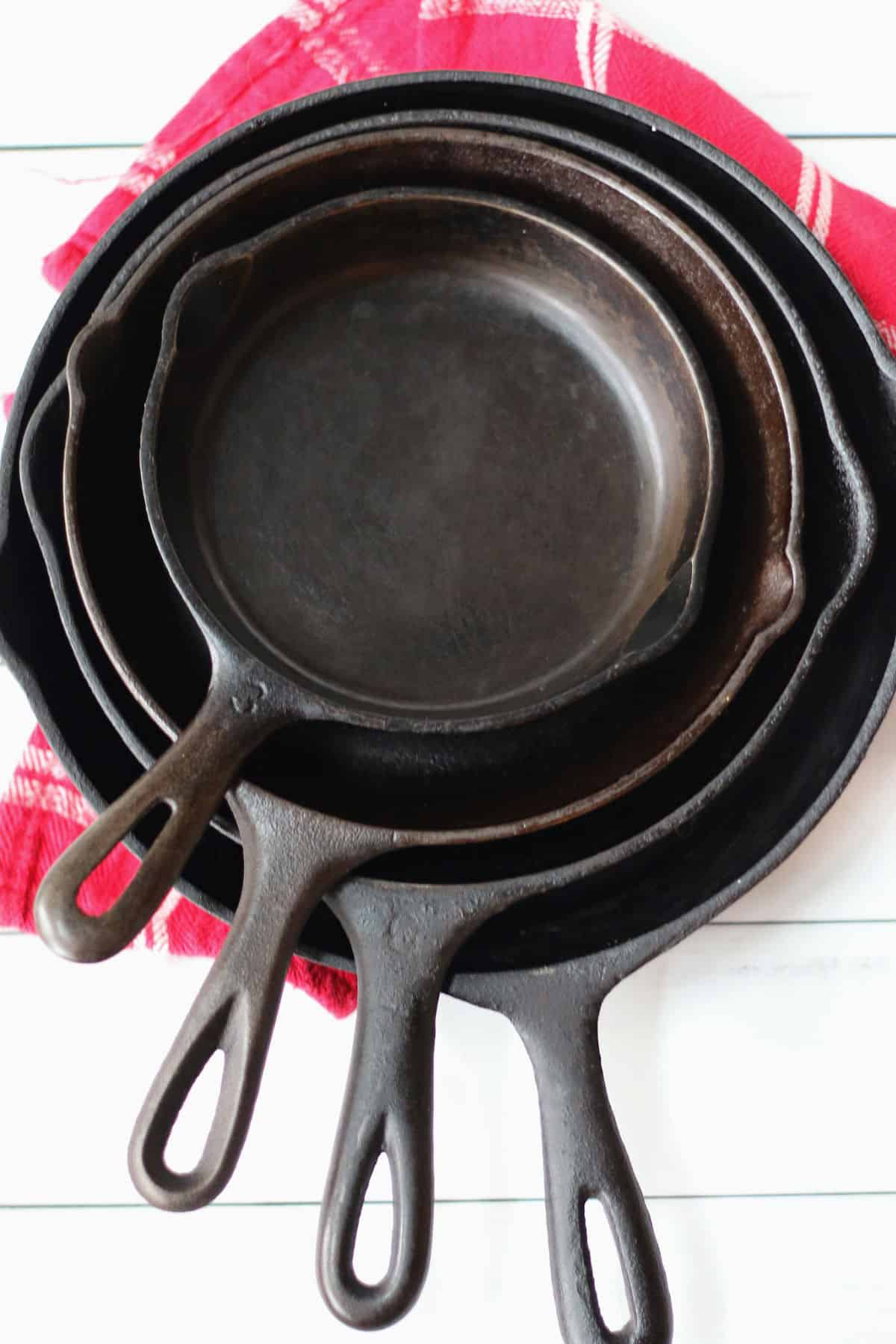a stack of four vintage iron skillets
